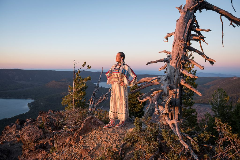 Native woman Acosia M. Red Elk in historic buckskin dress on top of Paulina Peak, Central Oregon, USA